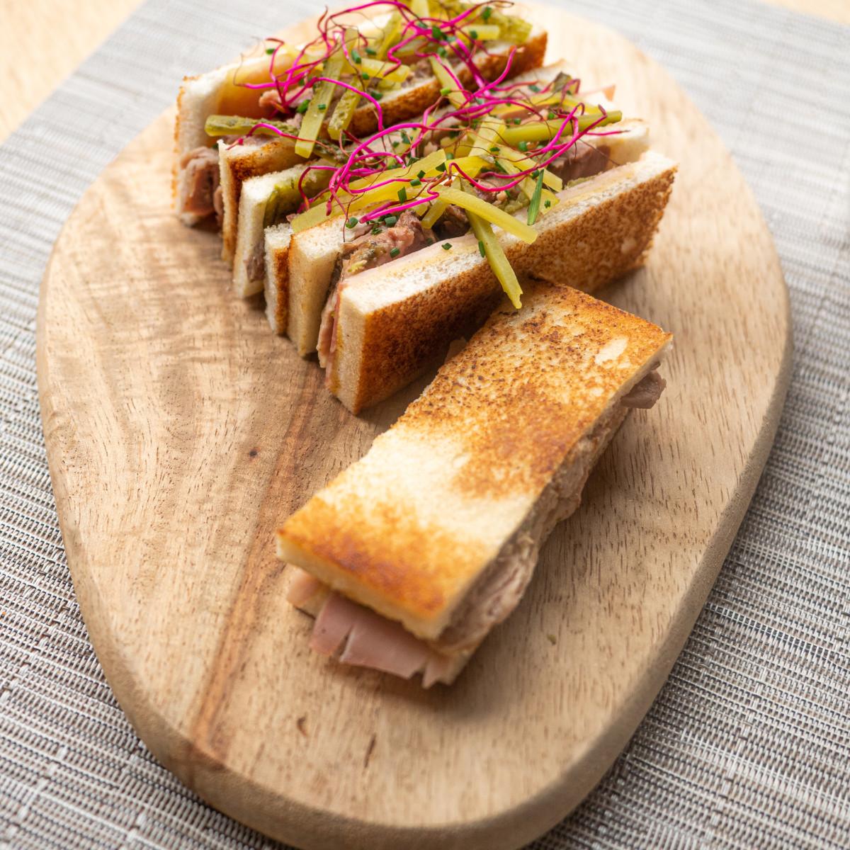 Planchado Cubano: cerdo marinado, jamón, queso fundido, pepinillos y mostaza